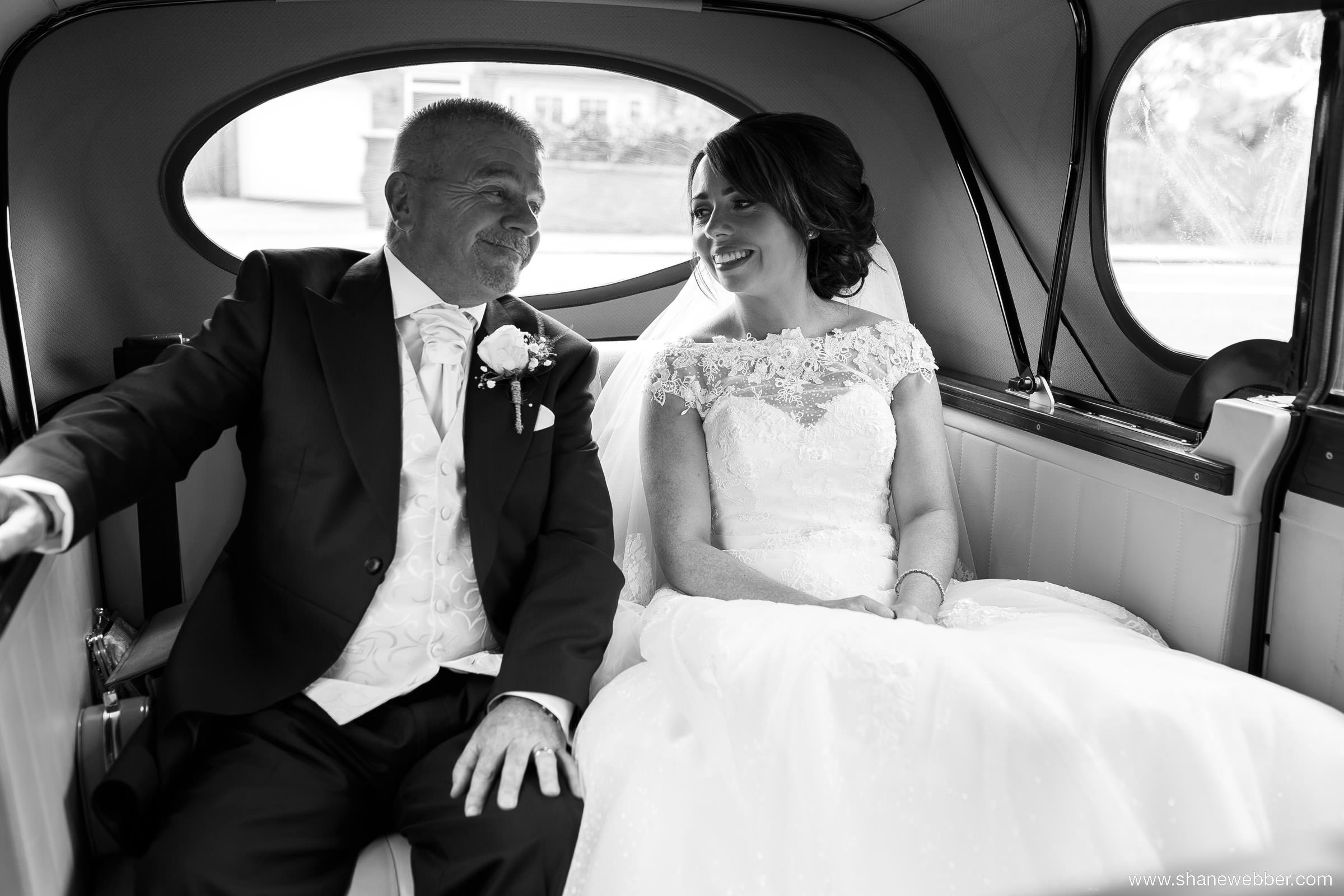 Black and white photo of bride with Dad in vintage wedding car