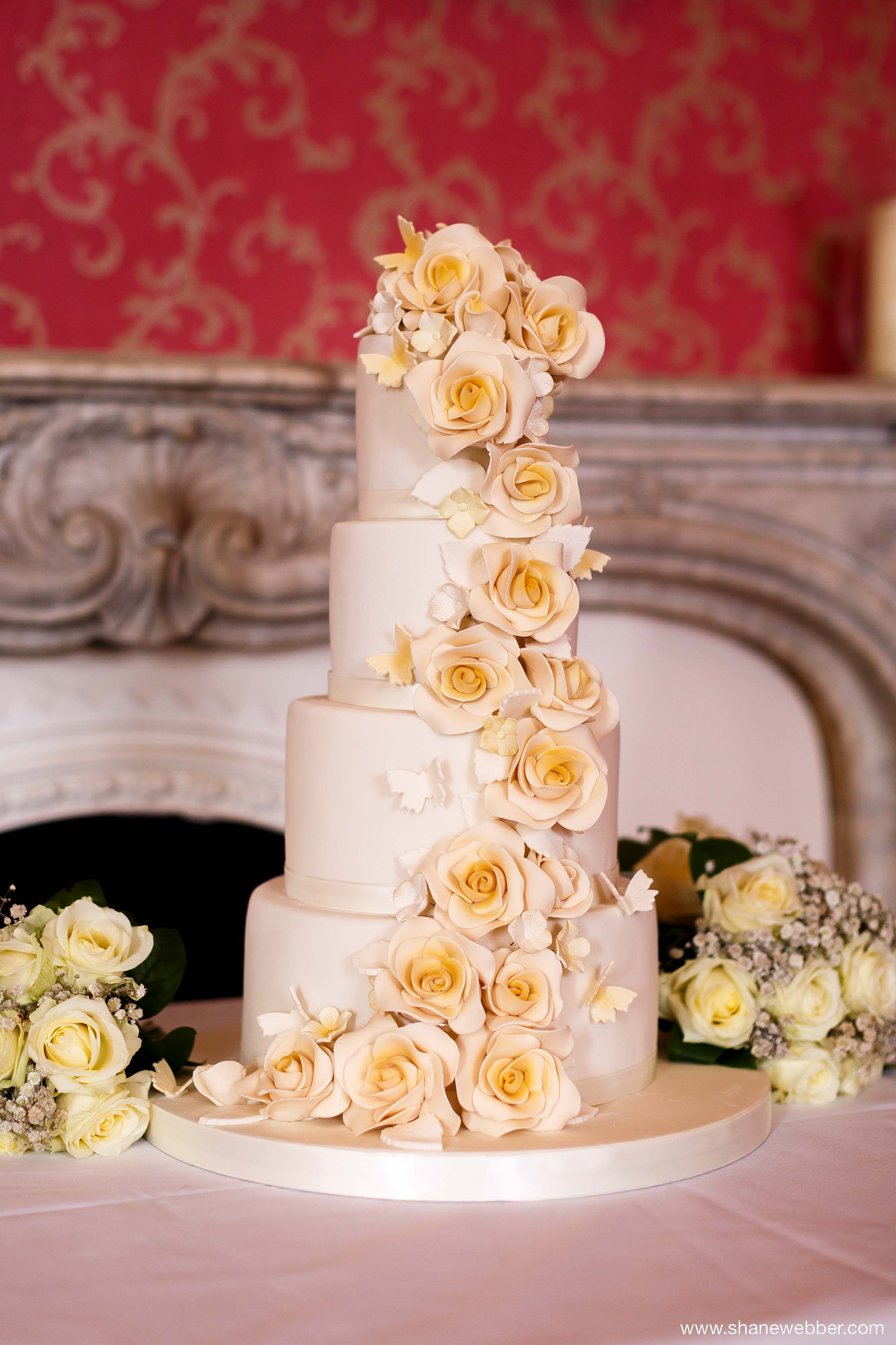 Four tiered wedding cake with cascading edible flowers