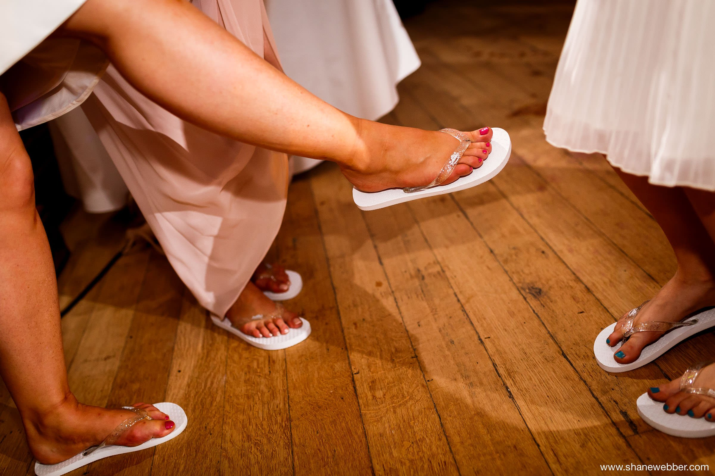 Guests dancing in white flip flops at wedding