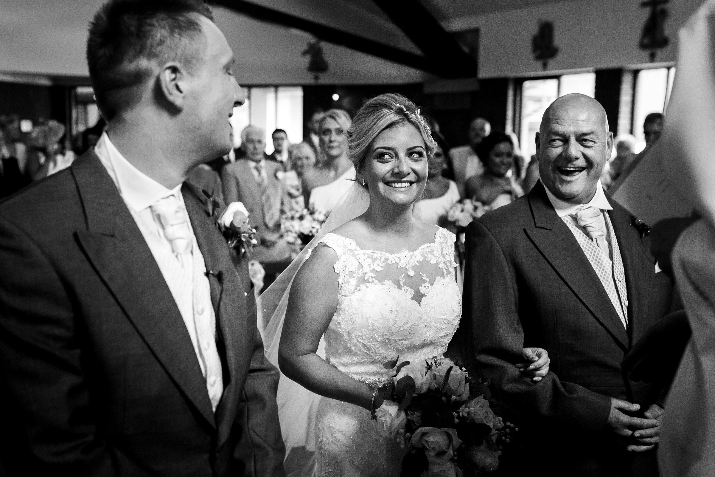 Natural wedding photo of bride walking down the aisle