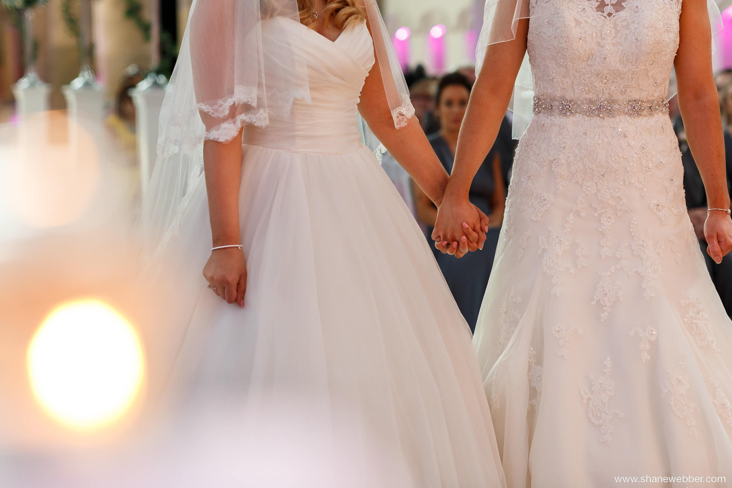 Two brides holding hands at wedding