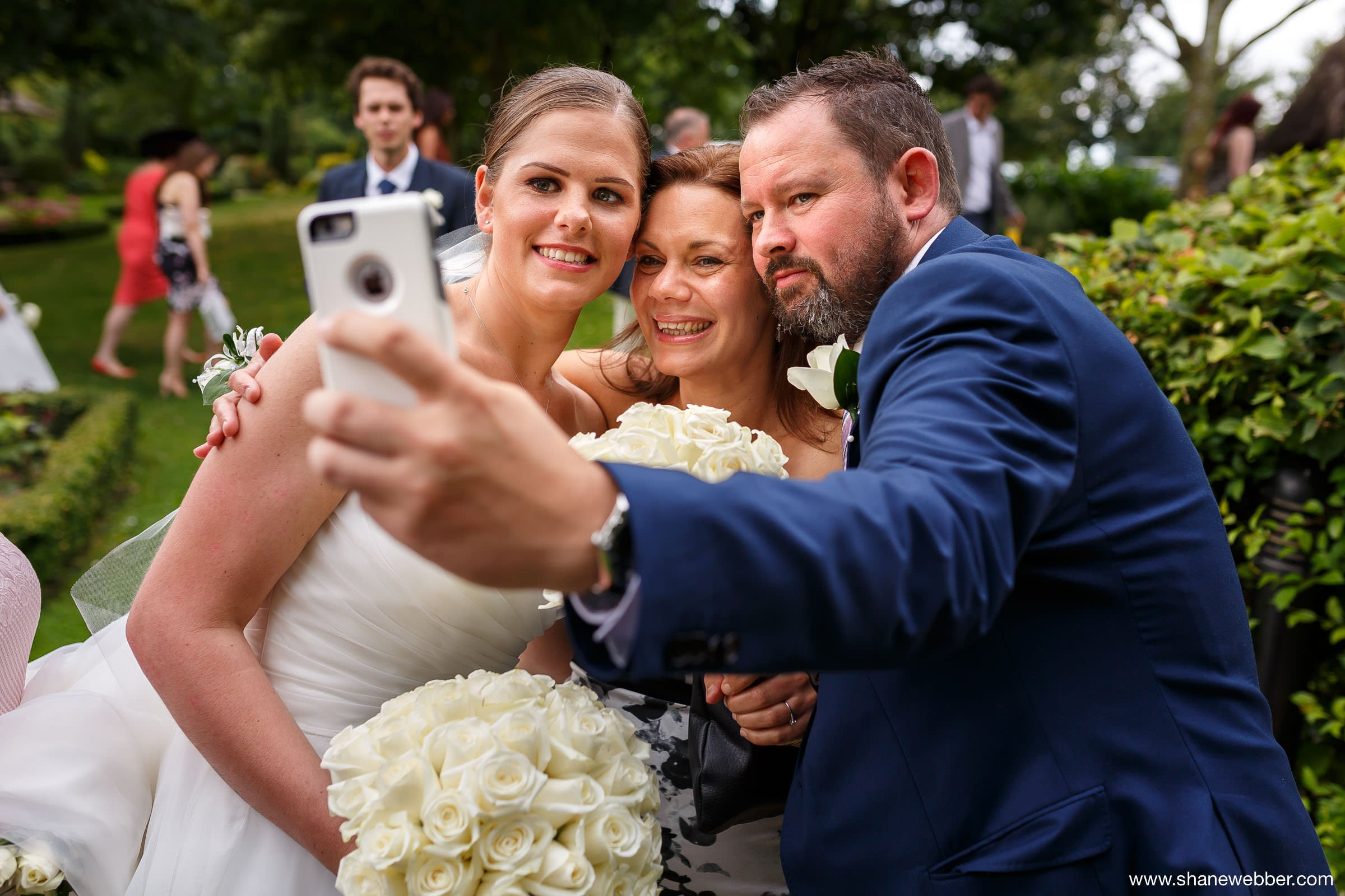 Natural wedding photo of guests taking a selfie