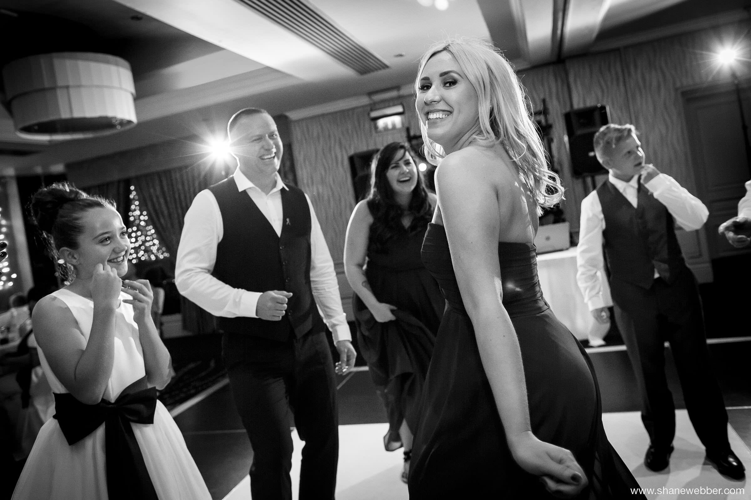 Natural wedding photography of guests dancing
