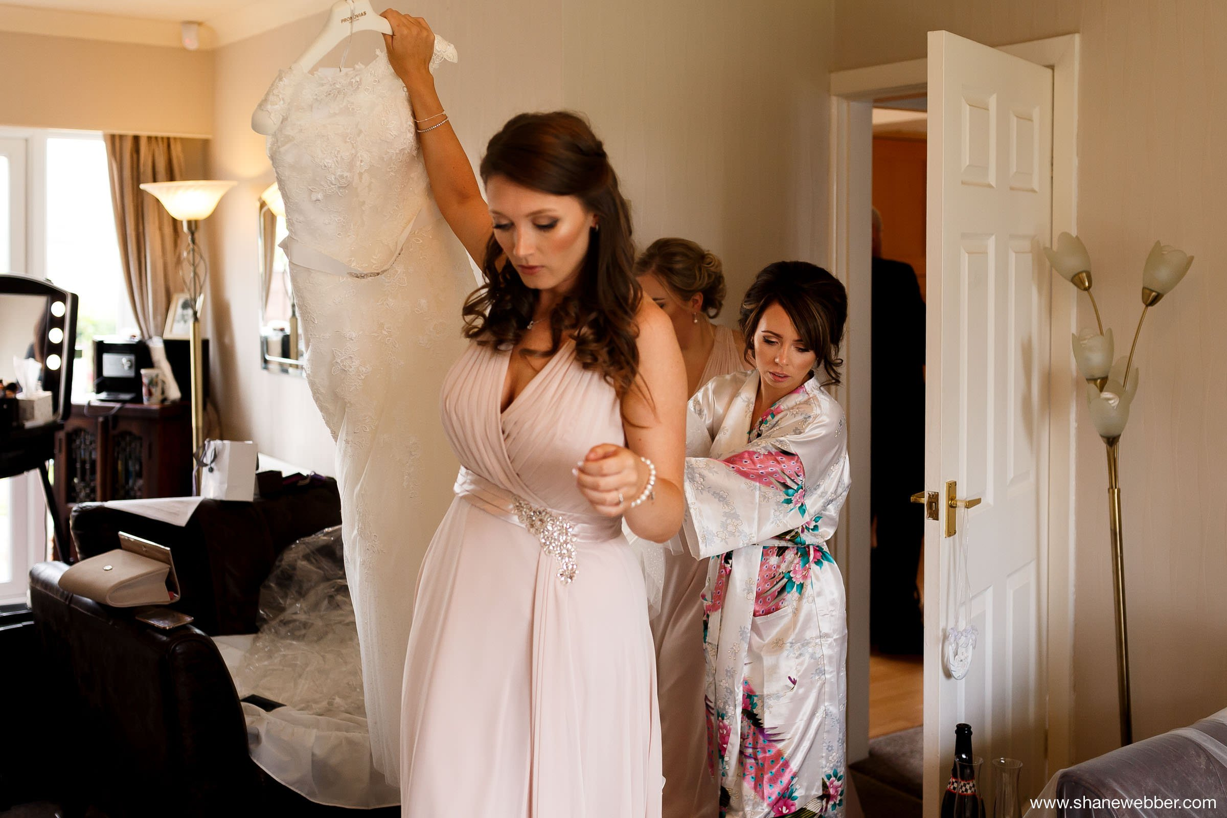 Photo of bridesmaids carrying wedding dress