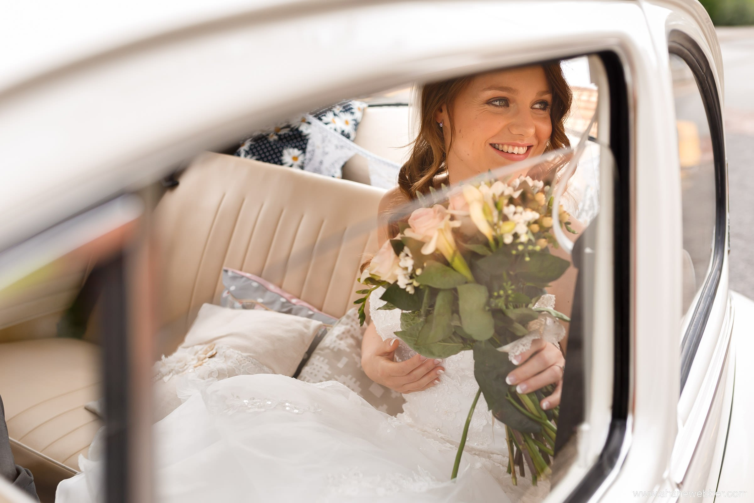 Beautiful portrait of bride in car at wedding