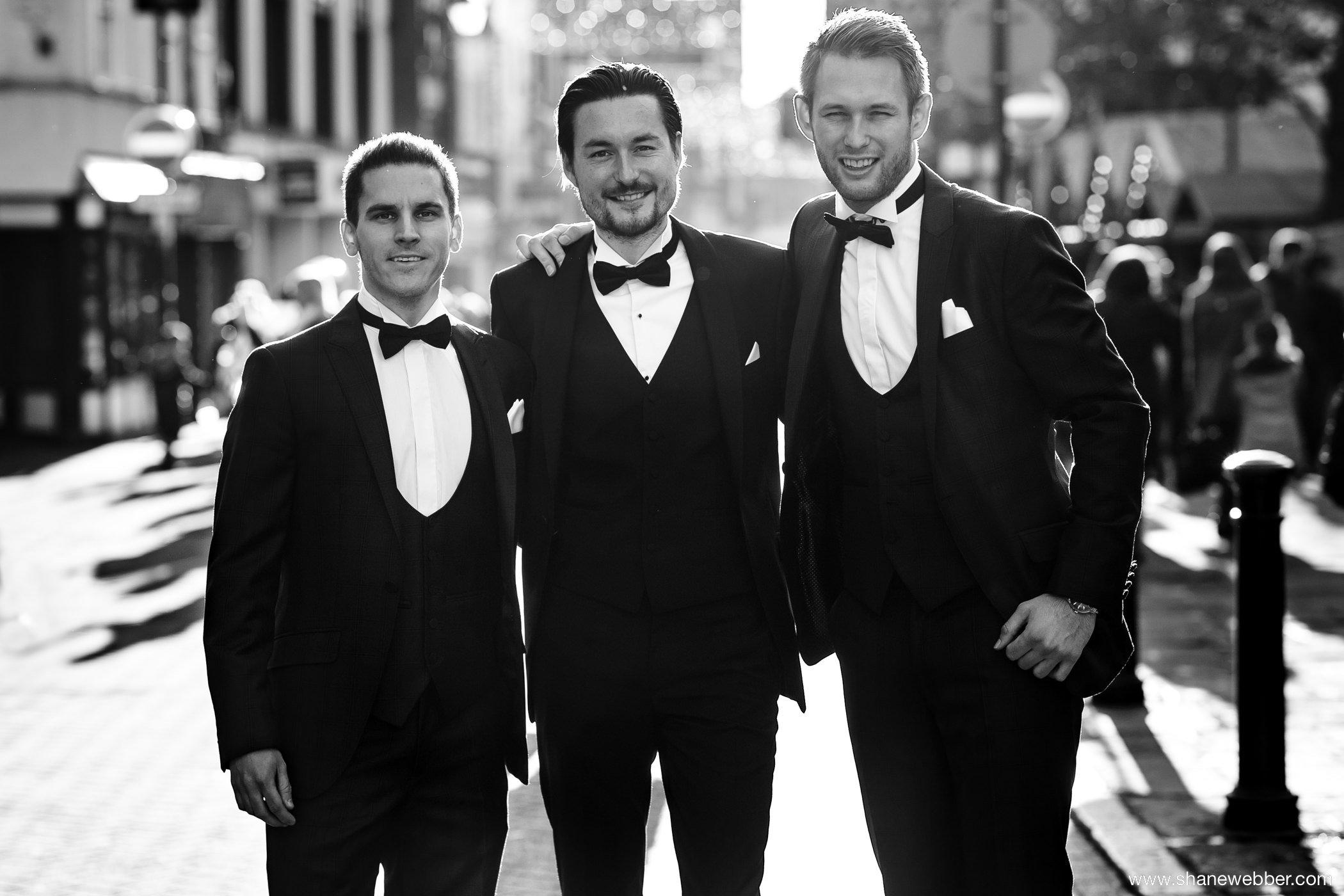 Groomsmen in black tie suits at wedding