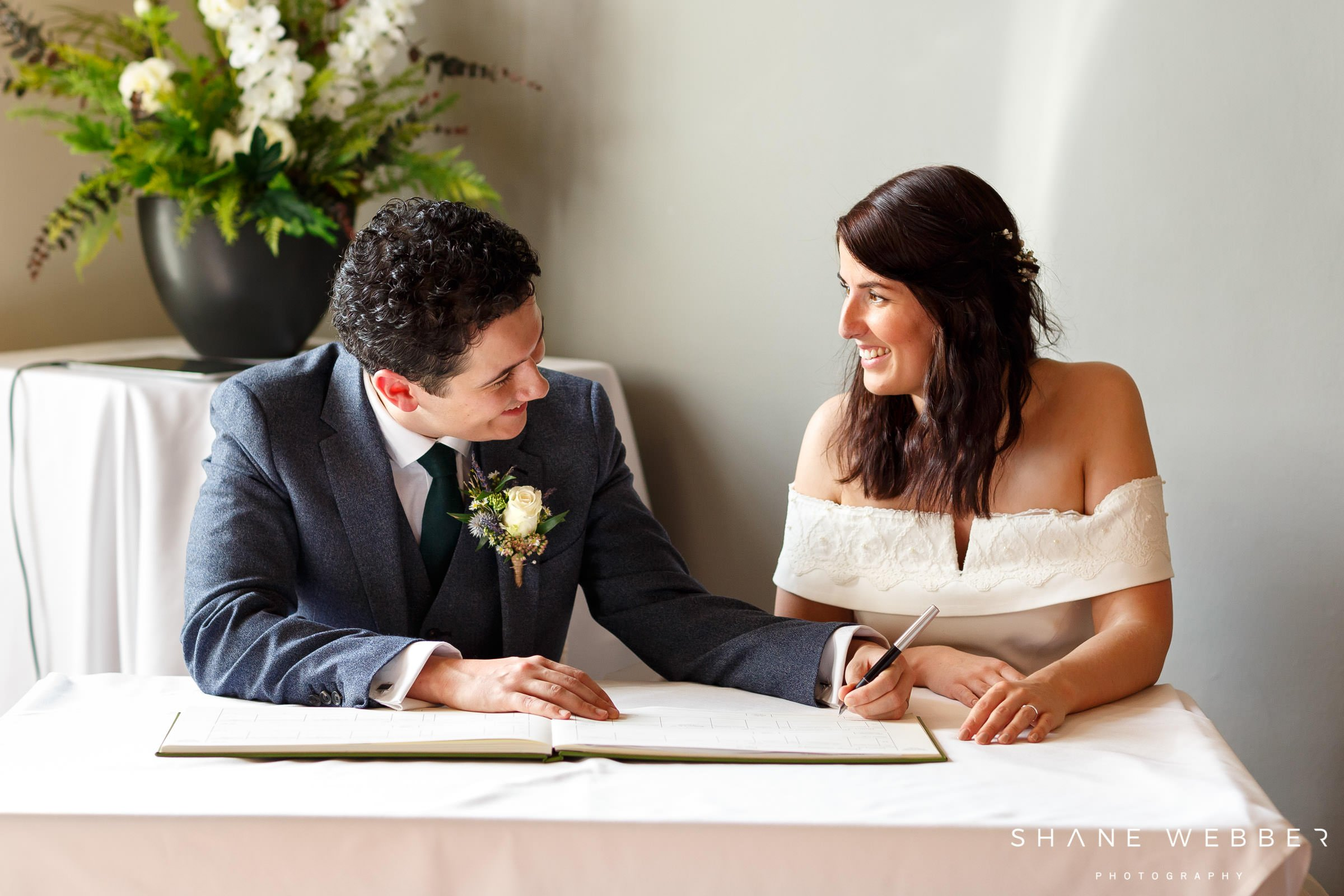 photo of bride and groom signing the register