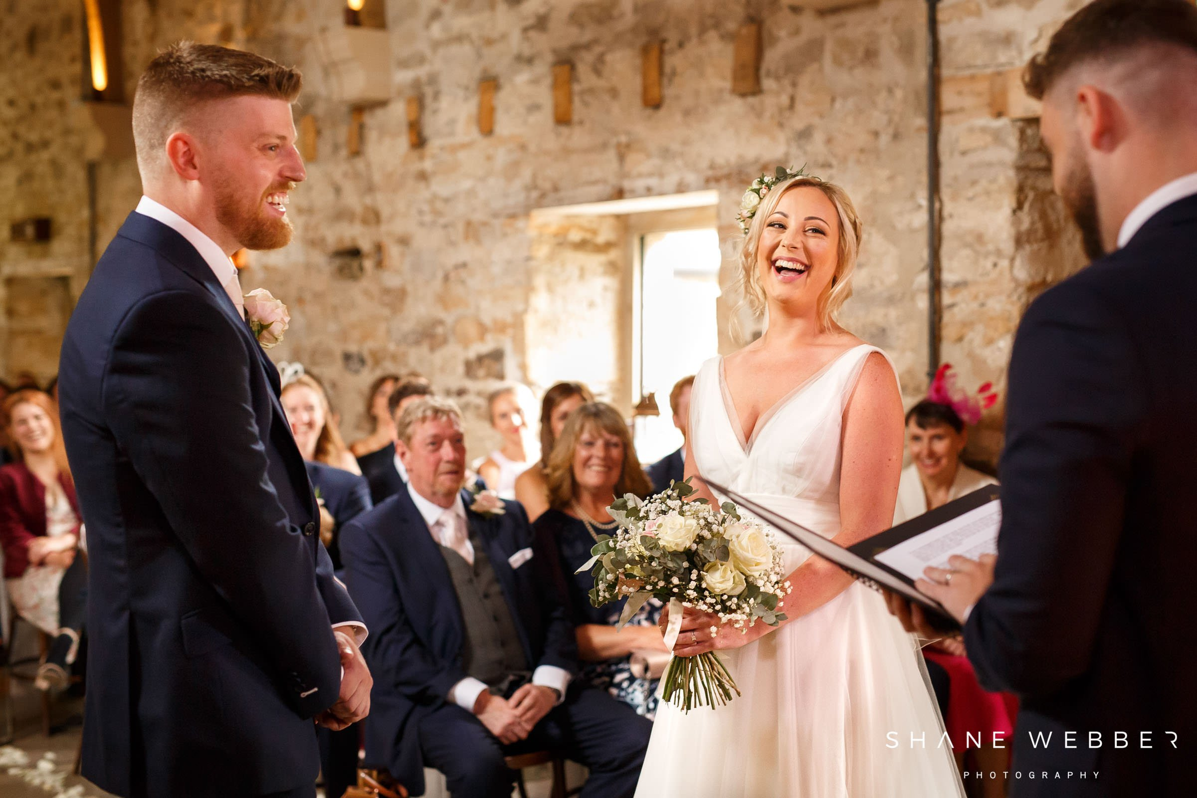 bride laughing during healey barn wedding ceremony