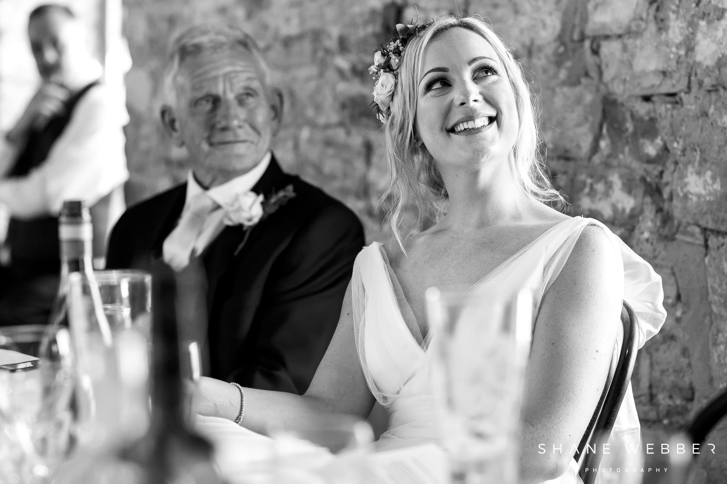 black and white photo of the bride during the grooms speech