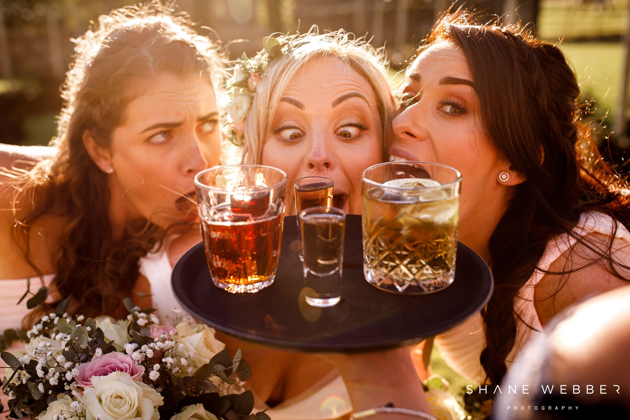 bride and bridesmaids doing shots