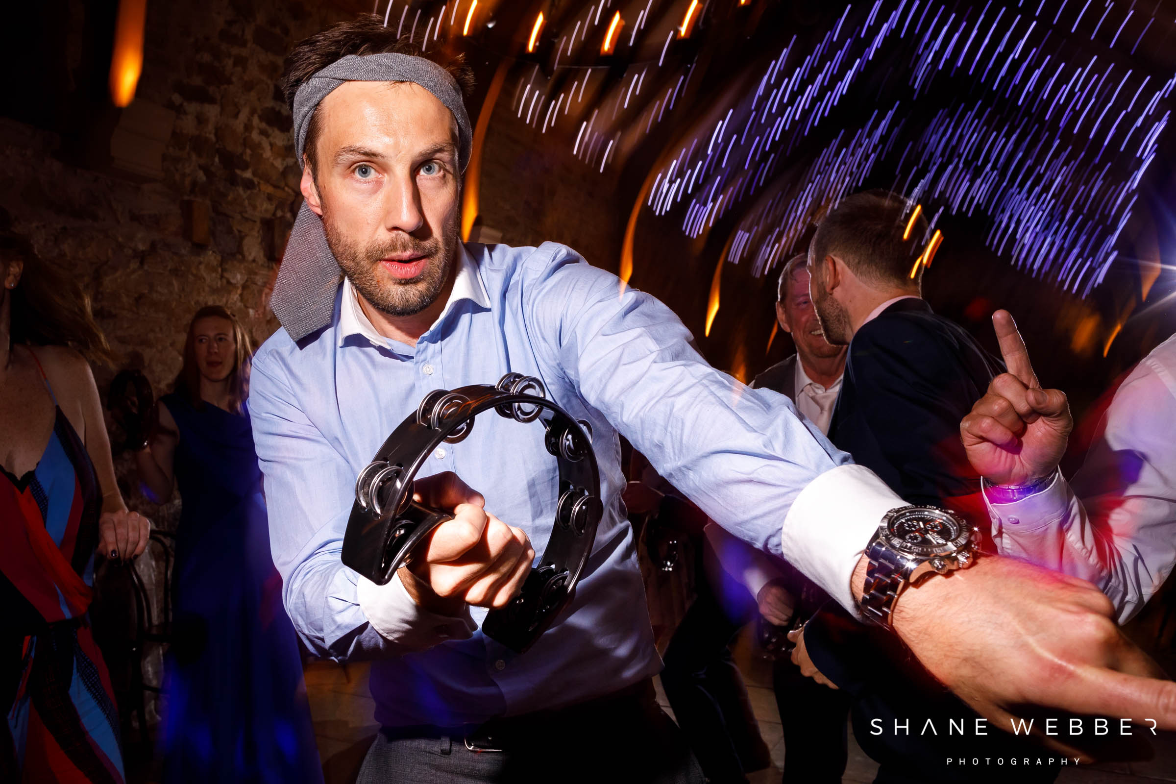 wedding guest at healey barn parties with tambourine and tie on his head