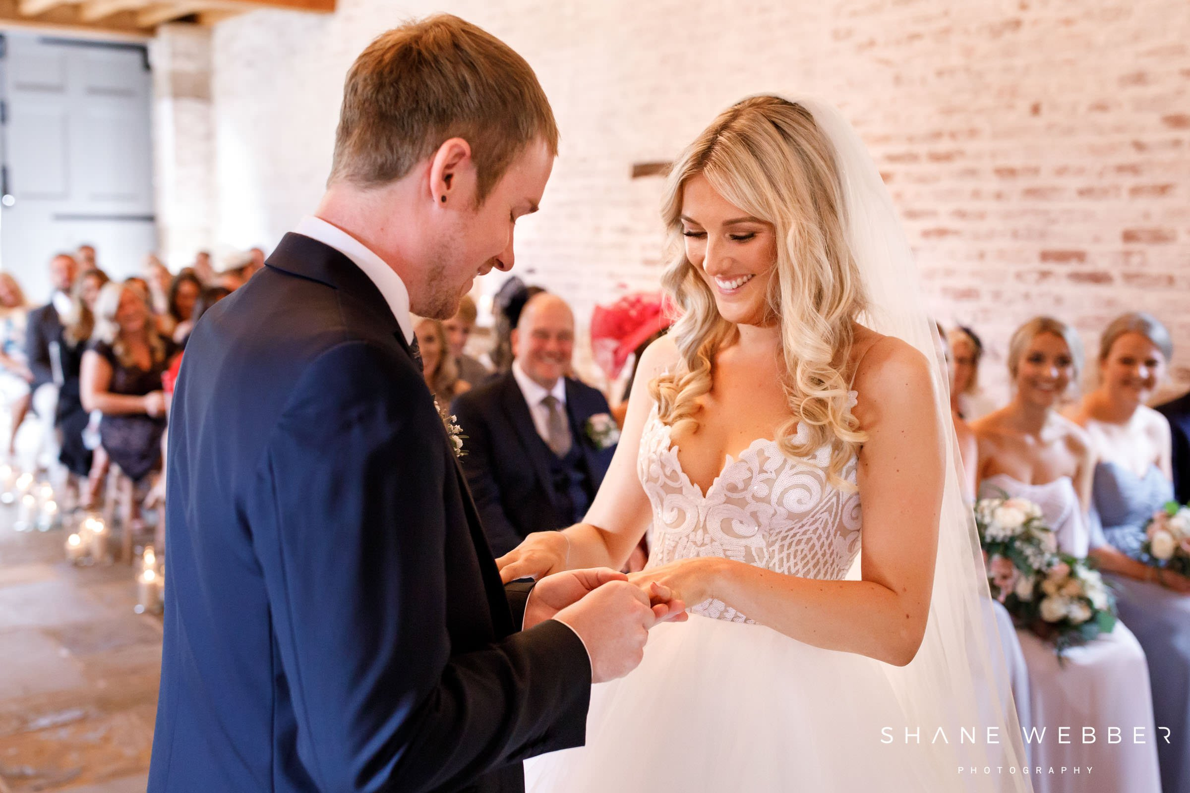 image of groom placing ring on brides finger