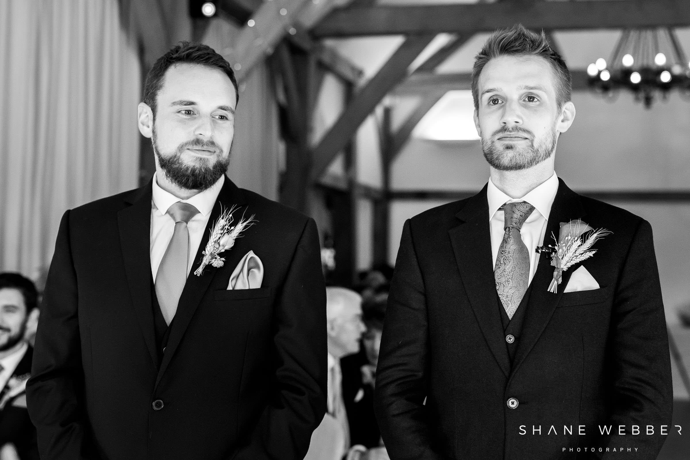 black and white photo of groom waiting at the aisle