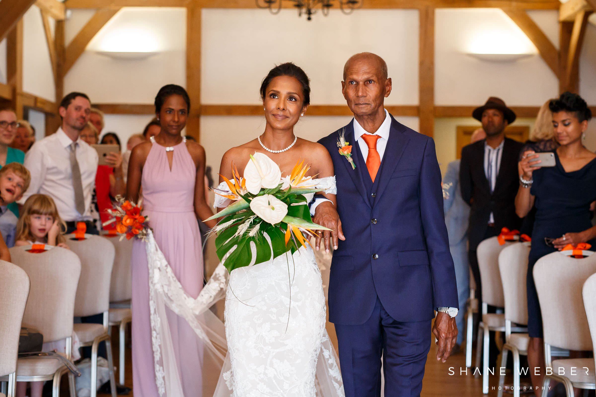 bride walking down the aisle with a tropical bouquet